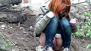 Cute shaved redhead in jeans pisses outdoors